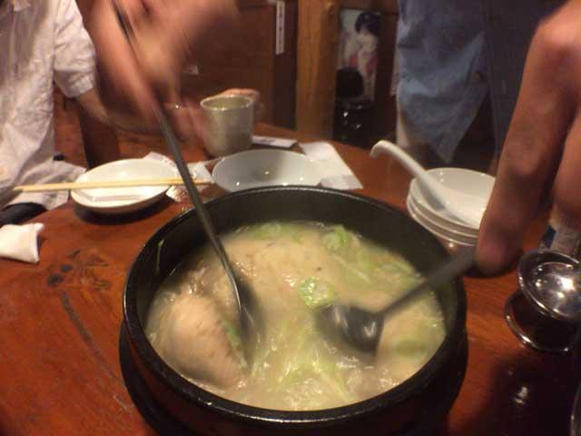 サムゲタンの鶏肉を崩すオジサン