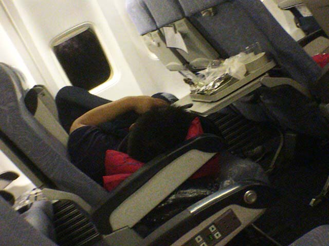 飛行機の機内で寝る中国人